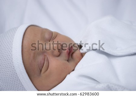 A close up shot of a new born baby. He lays asleep on a white backdrop in white clothing to provide space for copy. studio set up of one key light and a bounced flash with a shallow depth of field. - stock photo
