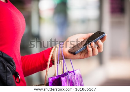 A close-up shot of a woman holding a cell phone or mobile phone whilst out shopping, - stock photo