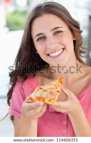 A close up shot of a woman looking into the camera as she holds a piece of pizza in her hand - stock photo