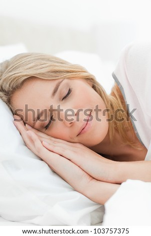 A close up shot of a woman resting in bed with her hands pressed on the pillow beside her head. - stock photo
