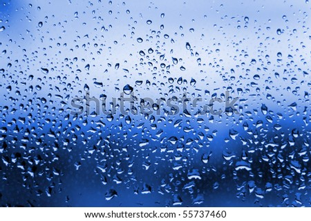 A close up shot of blue water droplets on a glass window pane. - stock photo
