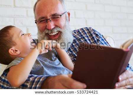 A close-up shot of lovely family. A grandfather and his grandson grinning broadly, man holding a book