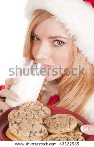 A close up shot of Mrs Santa drinking milk and holding cookies. - stock photo