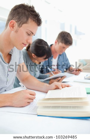 A close up shot of three students sitting together and studying