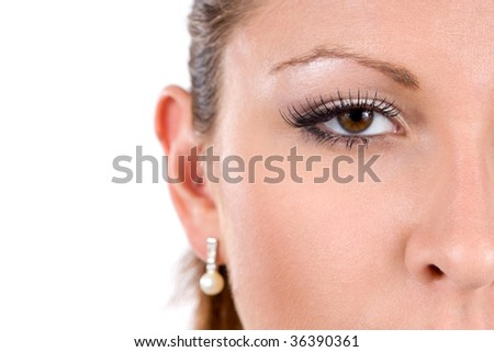A close-up showing half the face of a attractive woman with beautiful brown eyes.