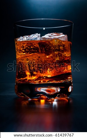 A close up studio shot of an single alcoholic drink on the rocks in a dark room