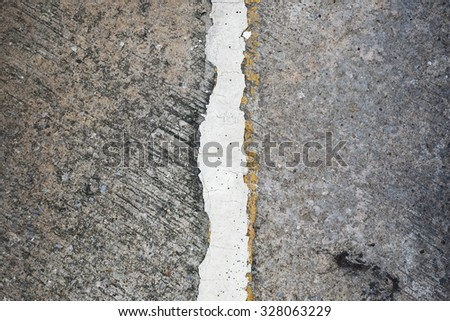A close up vertical view of cracked white-yellow line on asphalt road. Picture can be used as a background. - stock photo