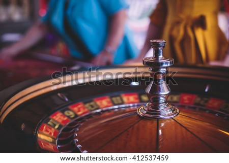 A close-up vibrant image of multicolored casino table with roulette in motion, with the hand of croupier, and a group of gambling rich wealthy people in the background  - stock photo