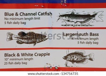 A close up view of a fishing limit size sign including large mouth bass, crappie, and catfish - stock photo