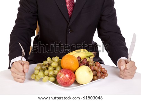 A close up view of a man holding his fork and knife getting ready to dig into a plate of fruit.
