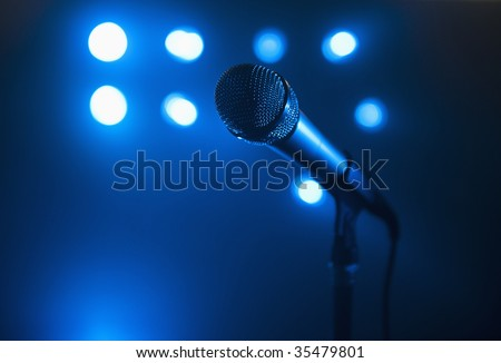 A close up view of a microphone and stand.  The background is blue and has several spotlights. Horizontally framed shot. - stock photo