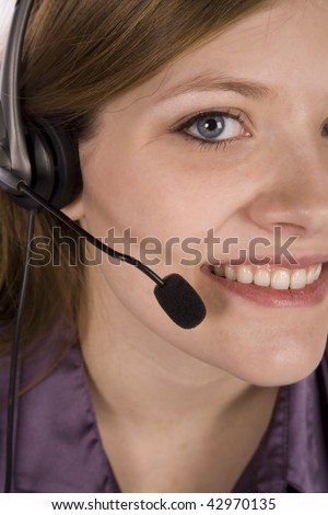 A close up view of a woman with her headset with a smile on her face. - stock photo
