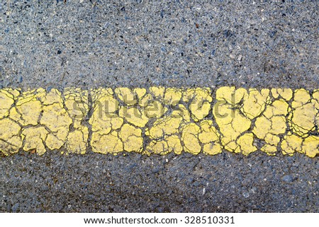 A close up view of cracked yellow line on asphalt road. Picture can be used as a background. - stock photo