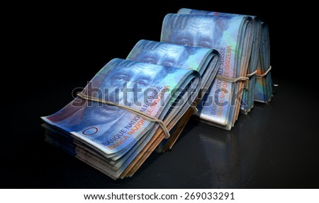 A close-up view of five wads of folded over stacks of chinese yuan banknotes each bound informally by a rubber band set out in a domino formation on an isolated dark studio background - stock photo