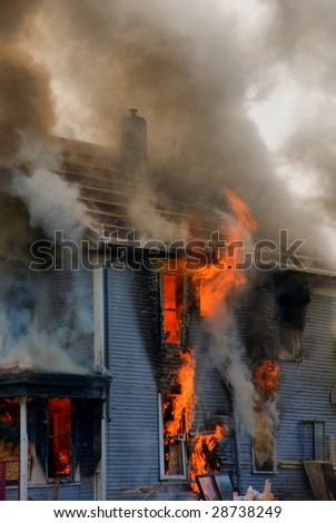 A close-up view of flames erupting out of the walls and roof of a house - stock photo