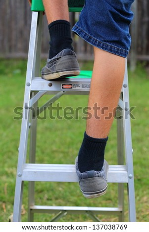 A close up view of someone climbing up a ladder - stock photo