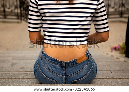 A close up view of the back of a sexy young girl with beautiful body in marine top and stylish high waist jeans in the park in summer. - stock photo