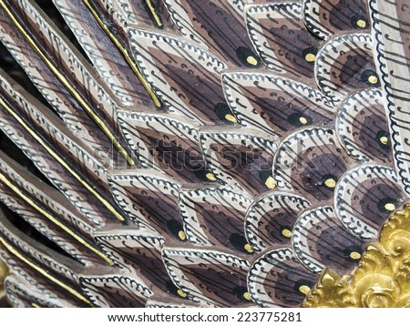 A close up view of the details of the tail-feathered section of an finely decorated dragon carved from wood. - stock photo