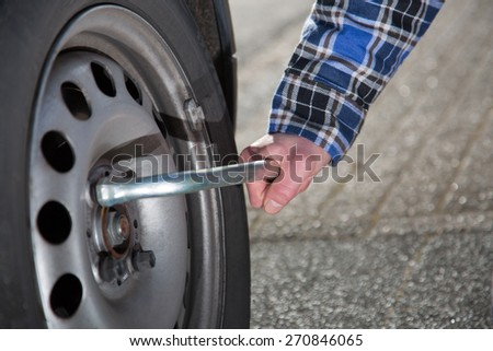 A close view from a mechanic who is opening the screws from a tire to change the tire on his car. - stock photo