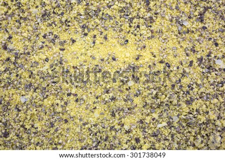 A close view of a mound of lemon pepper seasoning on a white background. - stock photo