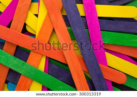 A close view of an assortment of colored craft sticks on a black background. arts and crafts, sticks, assorted colors, black, blue, green,  - stock photo