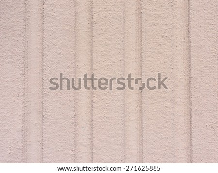 A close view of an exterior grooved beige wall. - stock photo