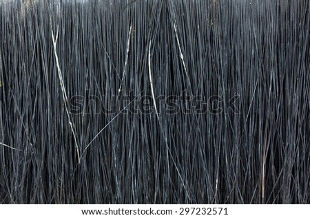 A close view of an old and used paintbrush bristles with segments of paint in the bristles.  - stock photo