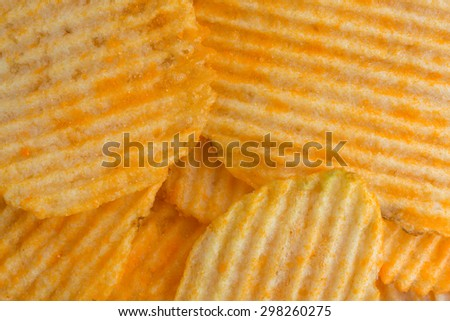 A close view of several cheddar cheese potato chips illuminated with natural light.