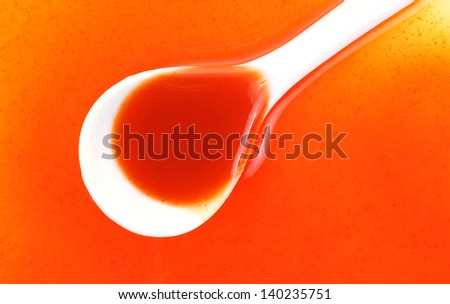 A close view of spilled hot sauce and partial spoon on top. - stock photo