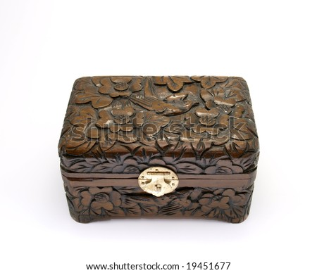 A closed brown ornate carved jewellry box with a gold clasp.