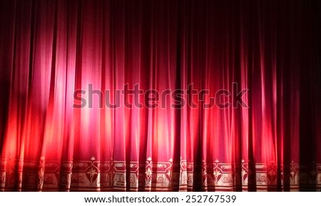 A closed red stage curtain in a small theater. Mobile photo. Mobilestock - stock photo