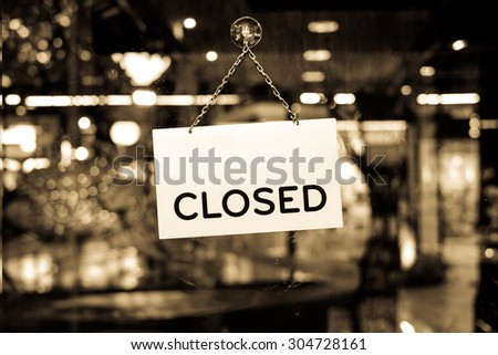 A closed sign hanging in a shop window with retro effect filter - stock photo