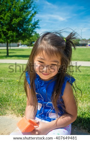 A closed up of little girl smiling and playing sand at public park  with blue sky background,filtered color tone in picture. - stock photo