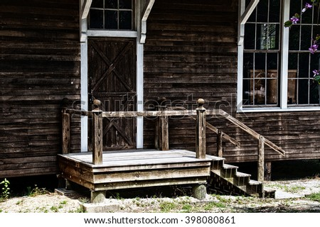 A closed wooden barn door at the top of a set of stairs on old weathered building.