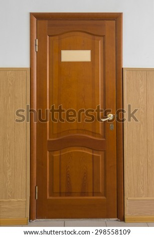 A closed wooden door with an empty plate.
