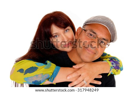 A closeuo photo of a happy middle age couple, the wife is hugging her husband from behind, isolated for white background.  - stock photo