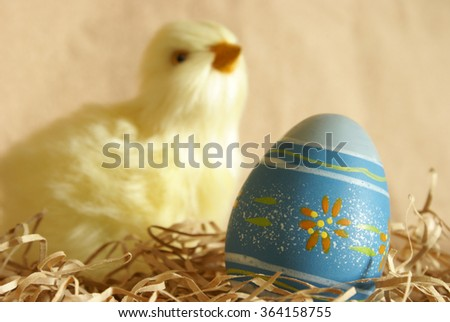 A closeup focus on a decorated Easter egg and a chick blurred in the background. - stock photo