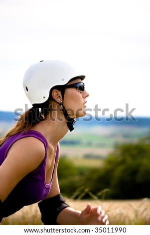 A closeup half face portrait of a young woman riding the roller skates in the country