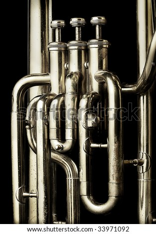 A closeup image of a well played and old tuba highlighting the valves