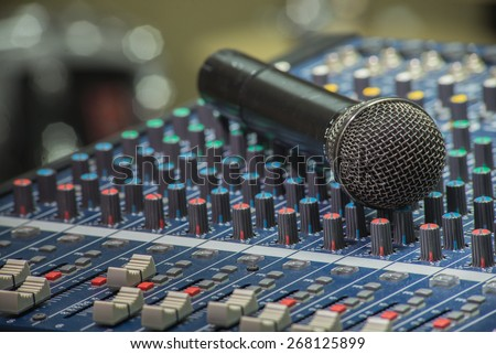 A closeup image of microphone on audio mixer's Music equipment - stock photo
