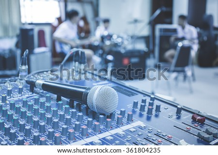 A closeup image of microphone on audio mixer's on musician blurred background in cooltone - stock photo