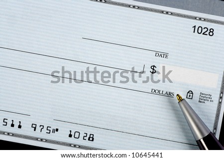 A closeup of a bank check with a pen.