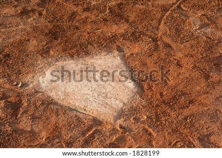 A closeup of a battered home plate at a baseball diamond. - stock photo