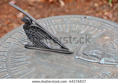 A closeup of a bird design on an old sundial. - stock photo