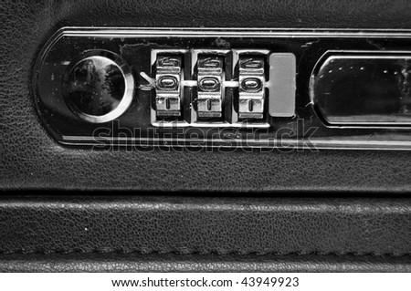 A closeup of a black briefcase three combination dial. - stock photo