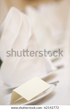 A closeup of a blank wedding placecard on ceramic white plate - stock photo