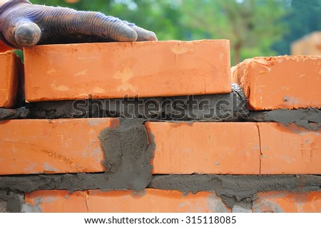 A closeup of a bricklayer worker installing red brick  - stock photo