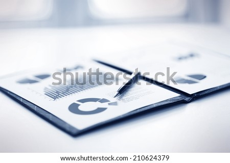 A closeup of a business financial chart with bar and pie graphs. A pen is on top. Can be used to represent business expenses, growth or revenue. - stock photo