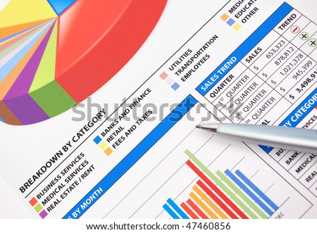 A closeup of a business financial chart with bar and pie graphs. A pen is on top. Can be used to represent business expenses, growth or revenue.