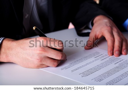 A closeup of a businessman singning a paper agreement - stock photo